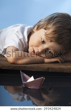 boy play in paper ship in water puddel - stock photo