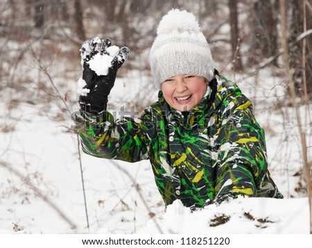 boy play snowballs  on winter wood