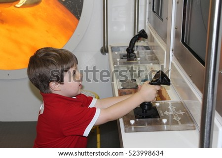 Boy Playing a Simulation Game at a Museum.