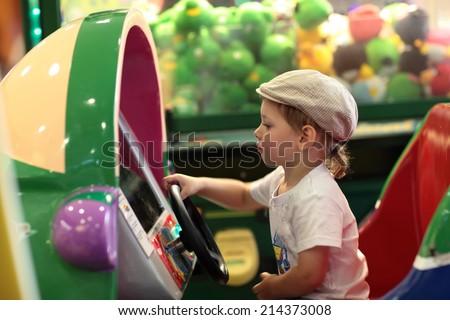 Boy playing arcade game machine at an amusement park - stock photo