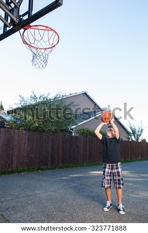 boy playing basketball at home - stock photo