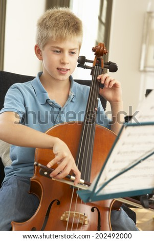 Boy playing cello at home - stock photo
