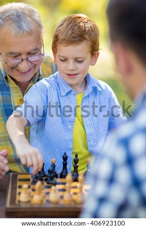 boy playing chess game at park - stock photo