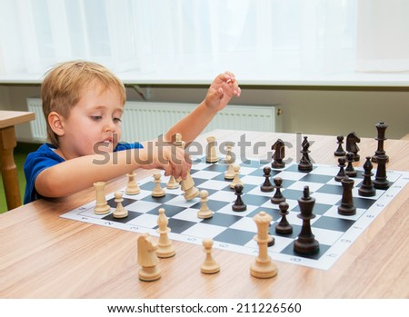 Boy playing chess in the class room - stock photo