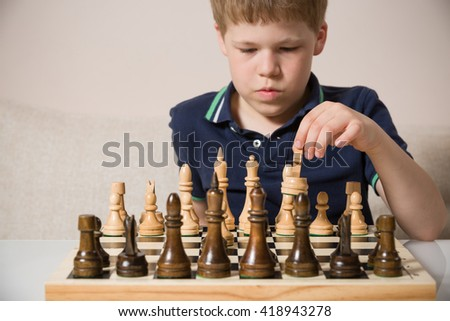 Boy playing chess in the room. Little clever child thinking while playing chess at home. Education concept. - stock photo