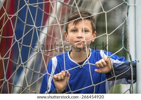 Boy playing football at the stadium, close-up portrait. - stock photo