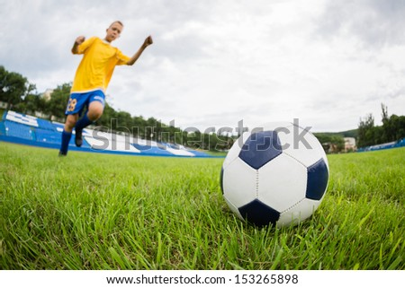 Boy playing football at the stadium with natural grass. Fish-eye lens. - stock photo