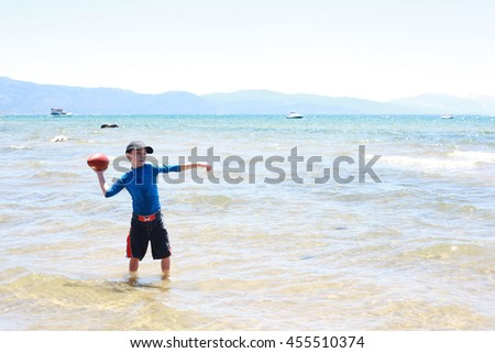 Boy playing football in the surf of Lake Tahoe - stock photo