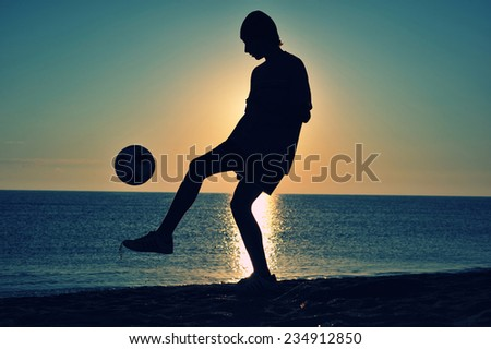 Boy playing football on beach at sunset  - stock photo