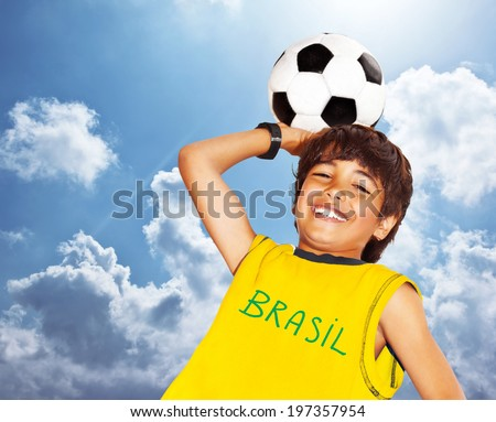 Boy playing football outdoor, happy child, teen goalkeeper enjoying sport game, holding ball, portrait of a preteen smiling and having fun, kids activities, little footballer over blue sky background - stock photo