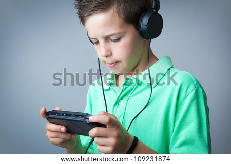 Boy playing game console against grey background - stock photo