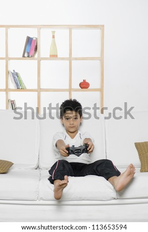 Boy playing handheld video game - stock photo
