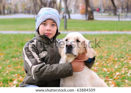 Boy playing in autumn park with a golden retriever.