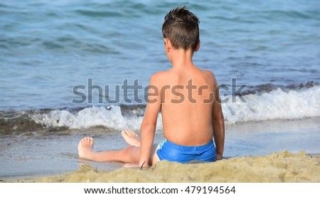 Boy playing in the sand on the beach.