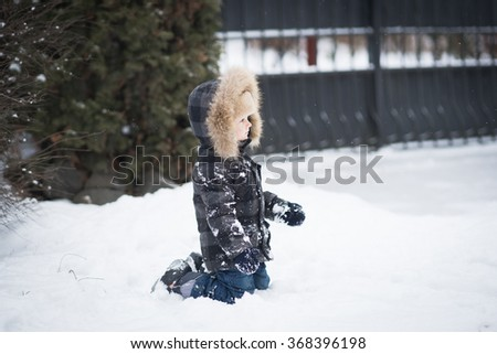 boy playing in the snow. Cold snowy winter. Happy childhood - stock photo