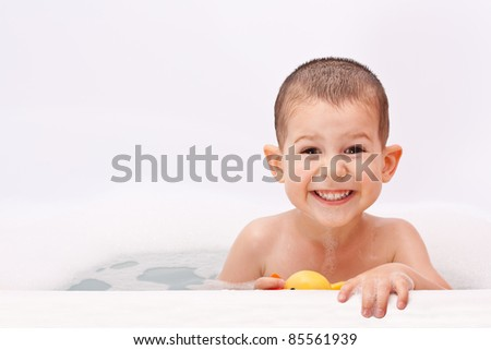 Boy playing in the water with toy - stock photo