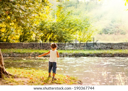 Boy playing next to a lake. - stock photo