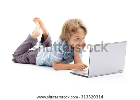Boy playing on a laptop computer concept for child internet safety, social media or education and homework - stock photo