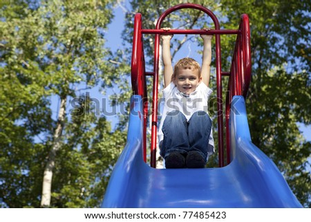 Boy Playing on a slide at the park - stock photo