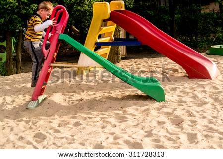 Boy playing on playground slide