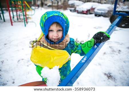 Boy playing on snowy street