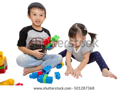 boy playing plastic block with his sister