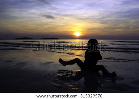 Boy playing sand on the beach while sunrise
