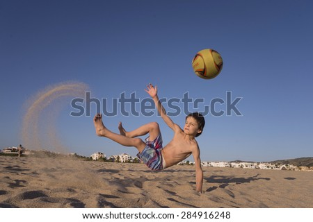 Boy playing soccer on the beach - stock photo