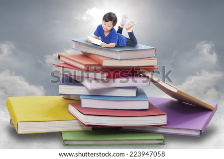 Boy playing tablet and lying on pile of books  - stock photo