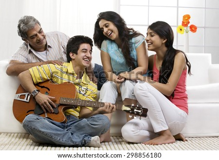 Boy playing the guitar for his family - stock photo