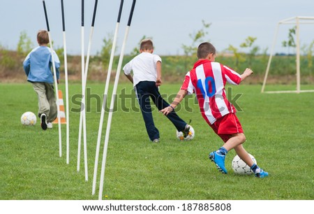 boy playing with a ball on the soccer field - stock photo