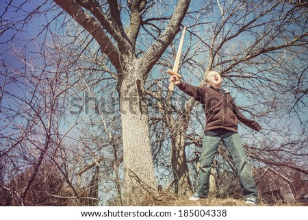 Boy playing with a sword outdoors - stock photo