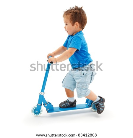 Boy playing with blue toy scooter (strong motion blur on leg) - stock photo