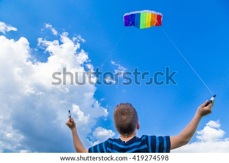 Boy playing with colorful kite against blue sky