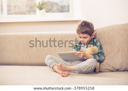 boy playing with digital tablet - stock photo