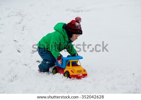 boy playing with his car and snow