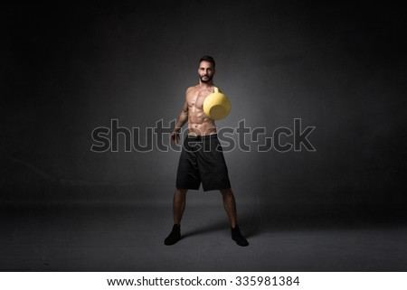 boy playing with kettlebell, dark background - stock photo