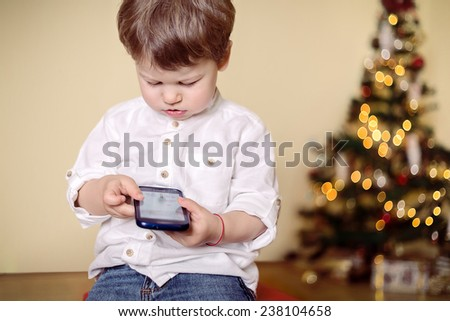 Boy playing with mobile phone - stock photo