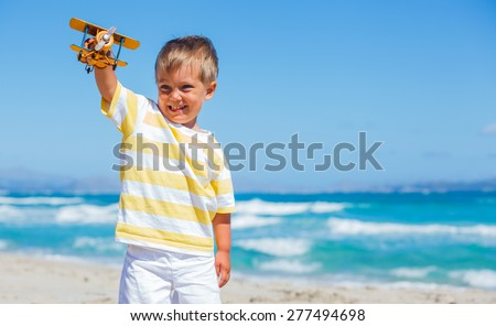 Boy playing with paper airplane on the tropical beach - stock photo