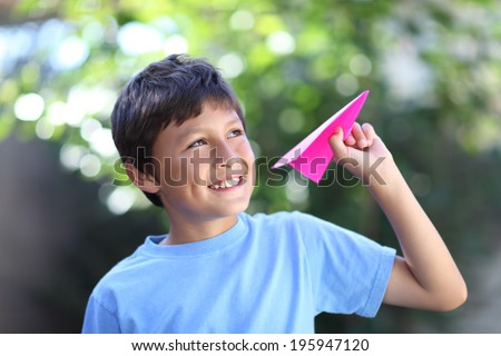 Boy playing with paper plane - with shallow depth of field - stock photo