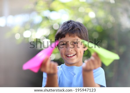 Boy playing with paper plane - with shallow depth of field