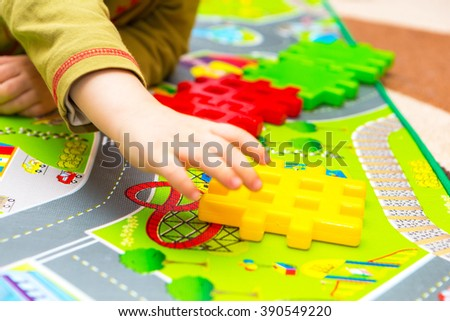 Boy playing with plastic blocks in home. Caucasian child build something with blocks