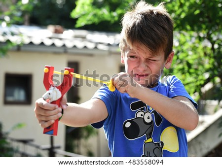 Boy playing with rubber slingshot