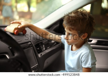 Boy playing with toy in car