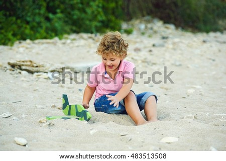 boy playing with toy plane in the sand