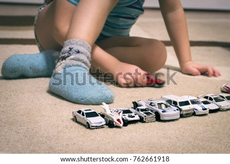 Boy playing with toy small cars on the floor