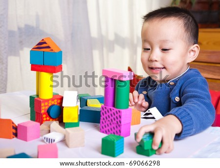 boy playing with wooden blocks - stock photo