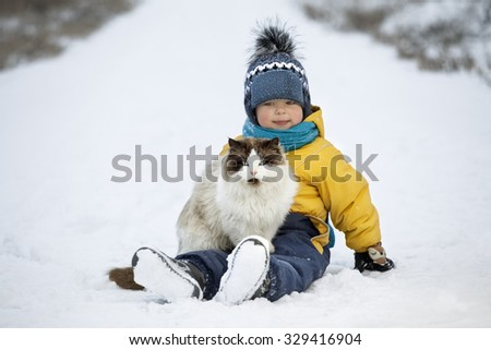 boy plays with a cat outdoors in winter
