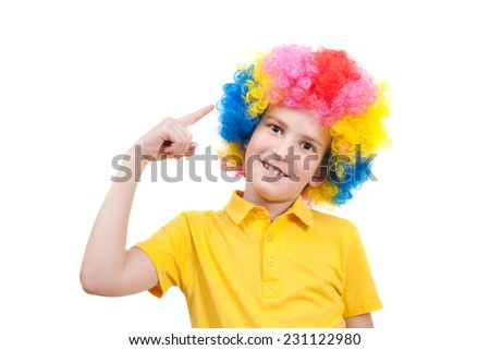 boy pointing his finger at his multi-coloured wig - stock photo