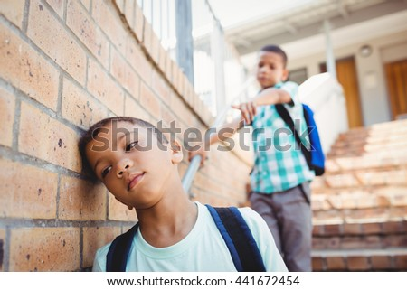 Boy pointing on another boy outside the school - stock photo